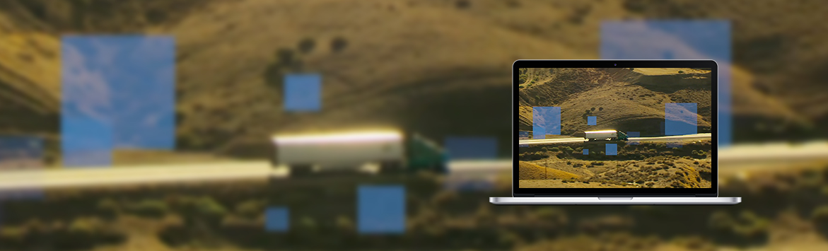 A banner image of a laptop screen featuring truck travelling along a highway surrounded by grass fields.