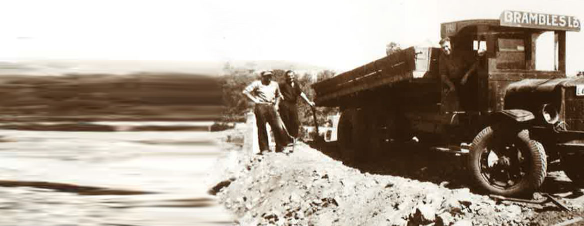 A sepia-toned historical image of two men with shovels standing by an old Brambles truck unloading materials