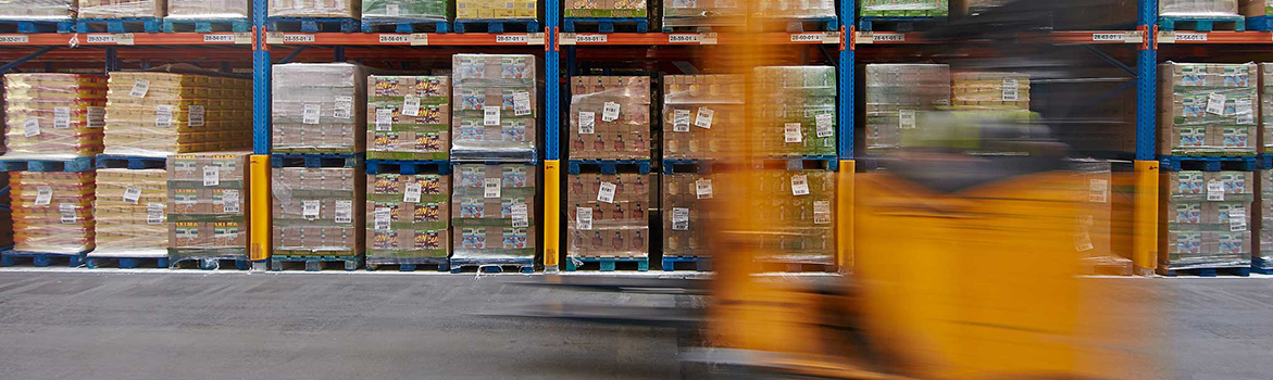 A photograph of a moving forklift in a warehouse in front of pallets of stock