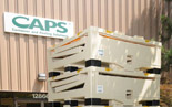 A photograph of a stack of 'Container and Pooling Solutions' boxes in front of the company logo