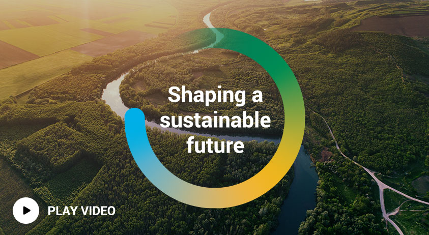 A thumbnail image for the Brambles' FY19 Sustainability Highlights video. The thumbnail features an aerial photograph of a river with the words Shaping a Sustainable Future inside a colourful circle. Also accompanied by 'Watch video' text.